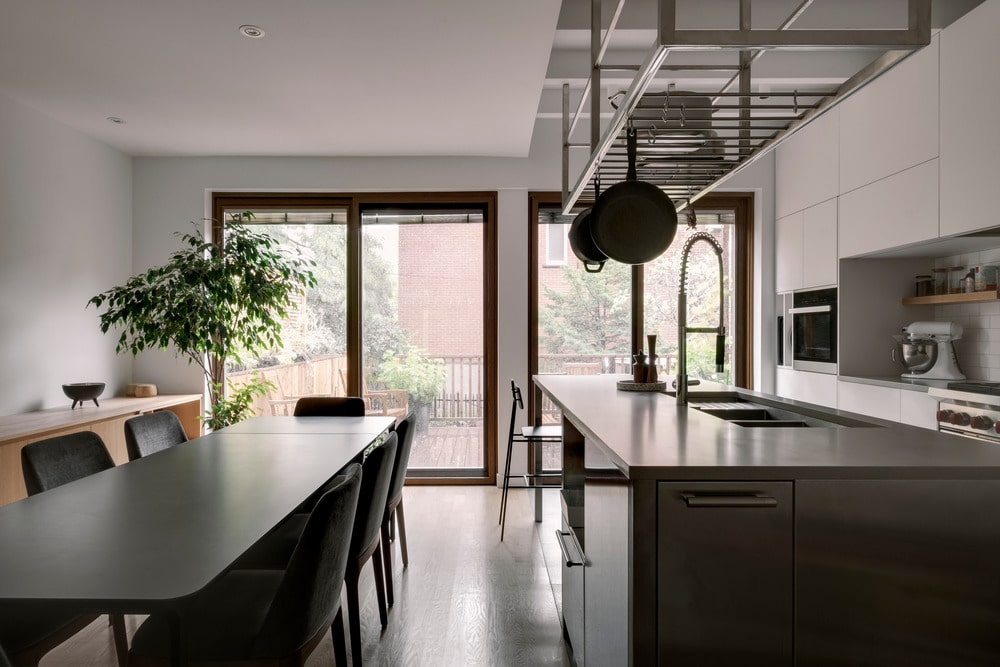 This is a view of the other side of the dining table with a large modern kitchen island topped with a hanging pot rack.