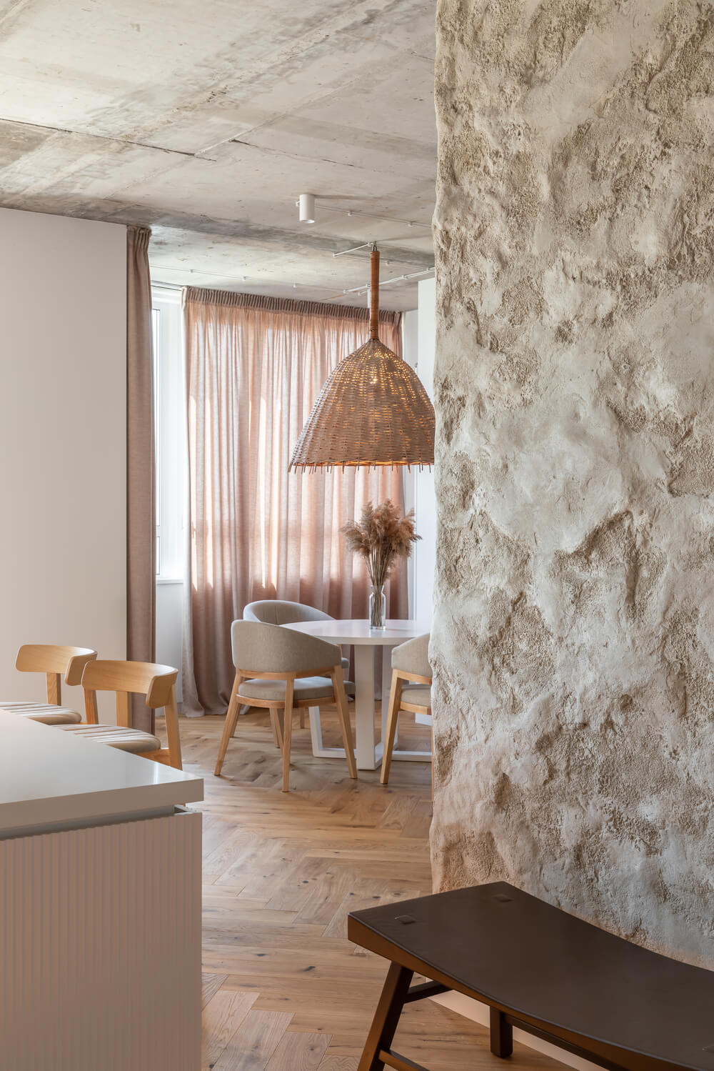 On the side of this dining room is a textured adobe wall.