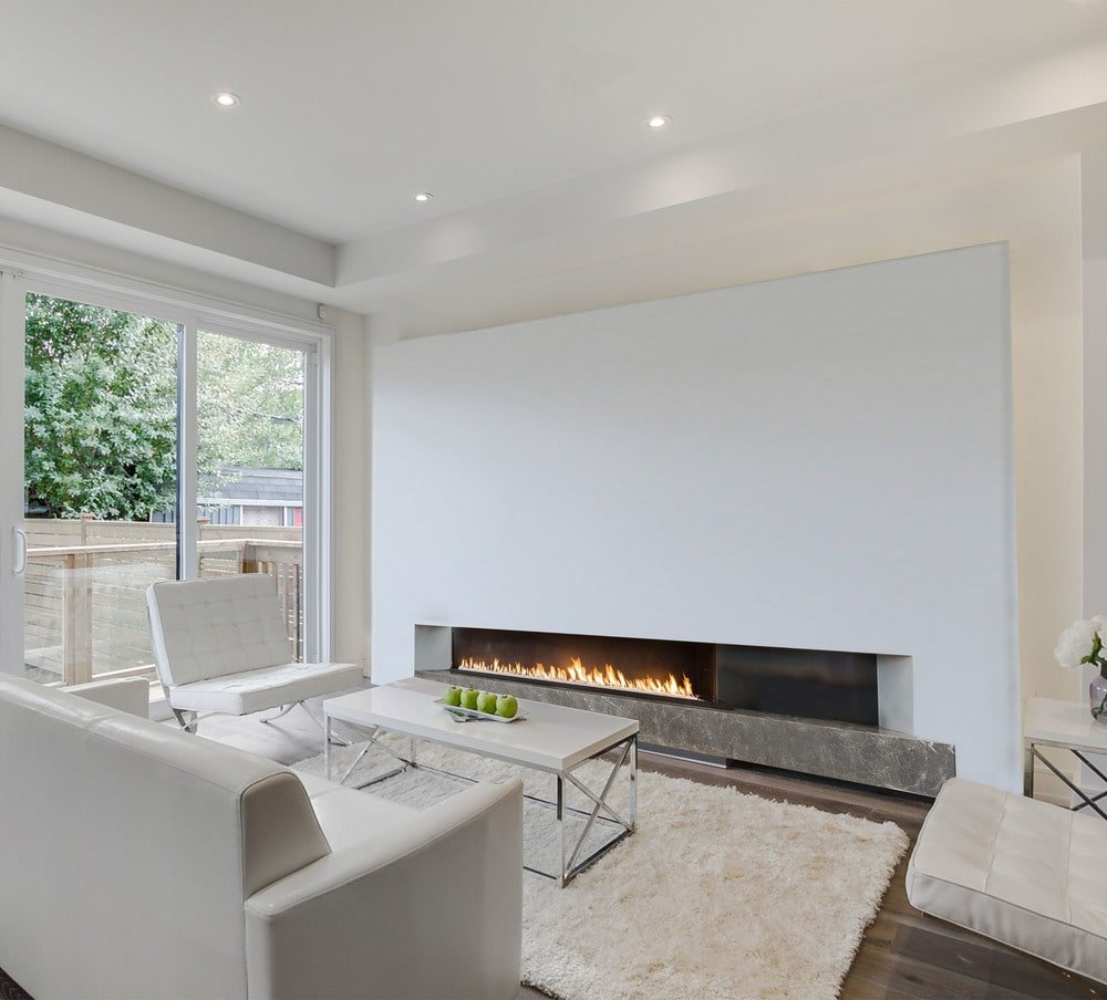 This is the family room with a beige sofa set warmed by the modern fireplace on the other side of the rectangular modern coffee table.