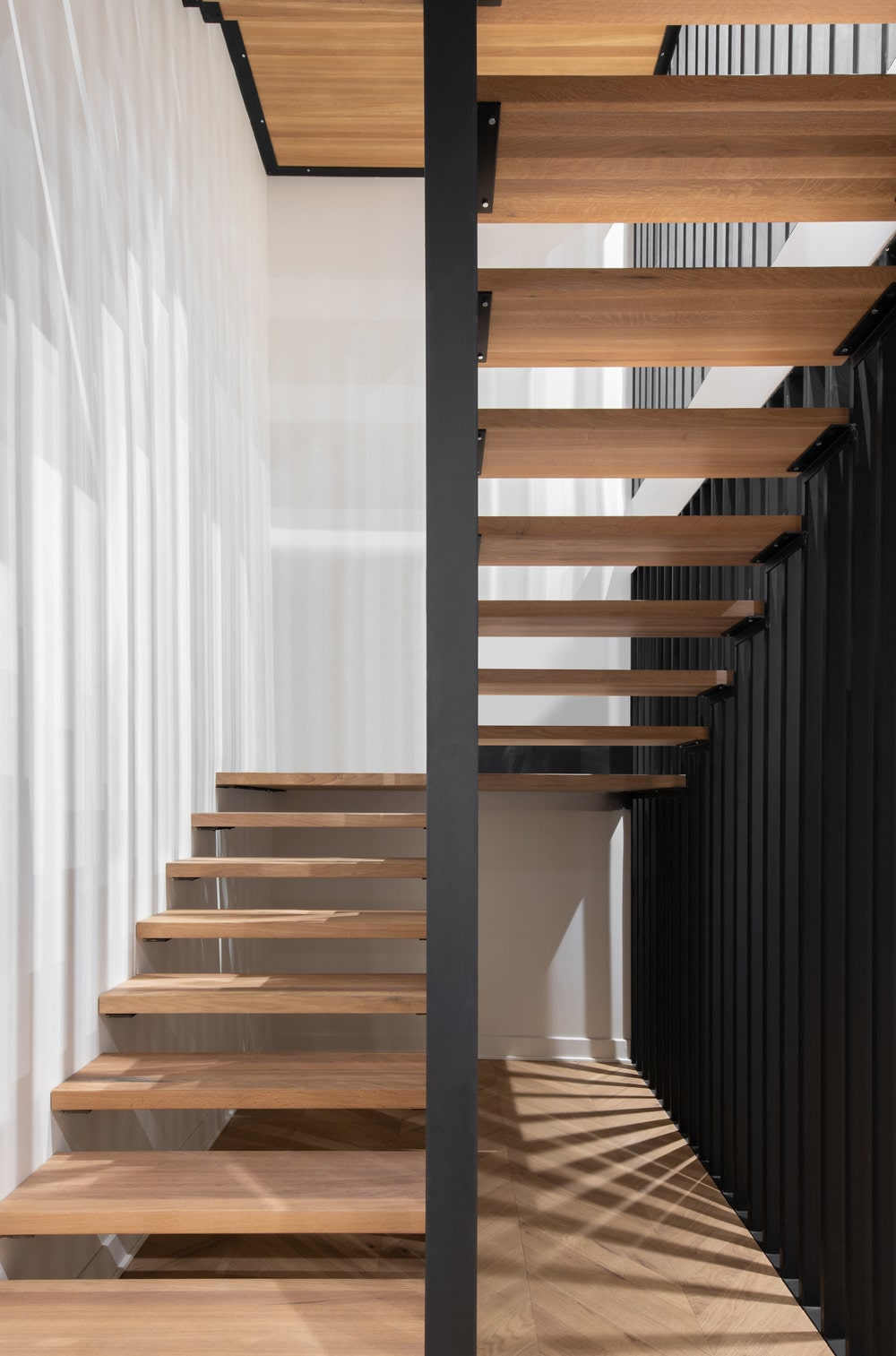 This is a close look at the staircase that has wooden steps that match the hardwood flooring contrasted by the black structures.