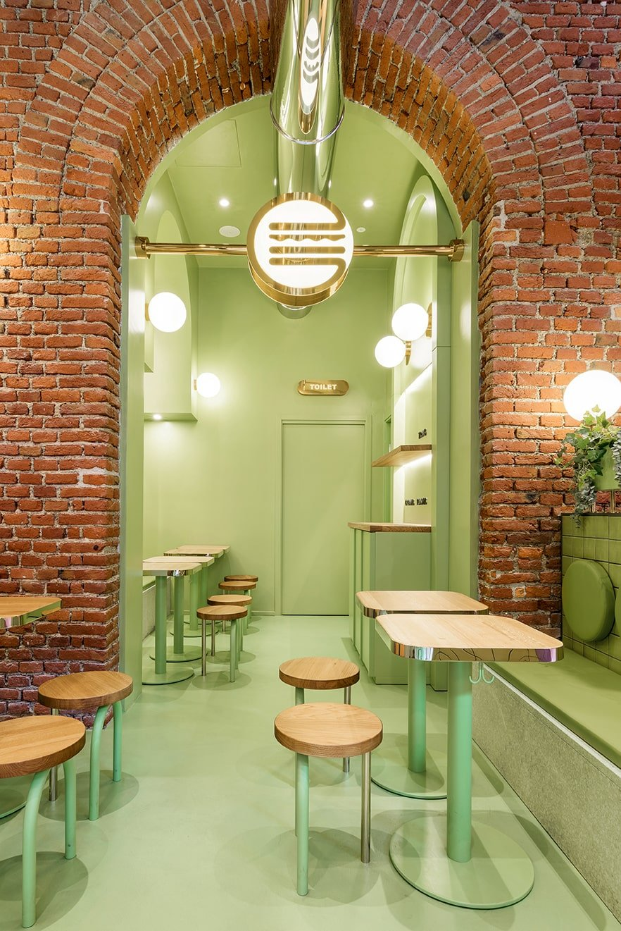 The brick archway leads to a small room fitted with more tables, chairs and a built-in cabinet on the side.