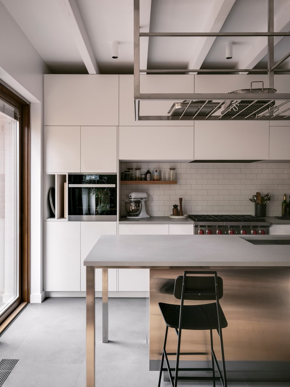 This is a view of the kitchen showcasing the attached modern table at the edge of the island and a view of the modern white cabinetry on the far side.