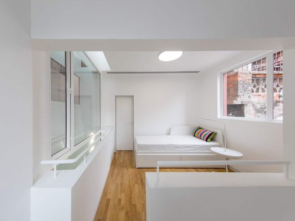 This is a look at the bright white bedroom that has has a consistent white tone on its bed, walls and ceiling complemented by the natural lighting of the window and the hardwood flooring.