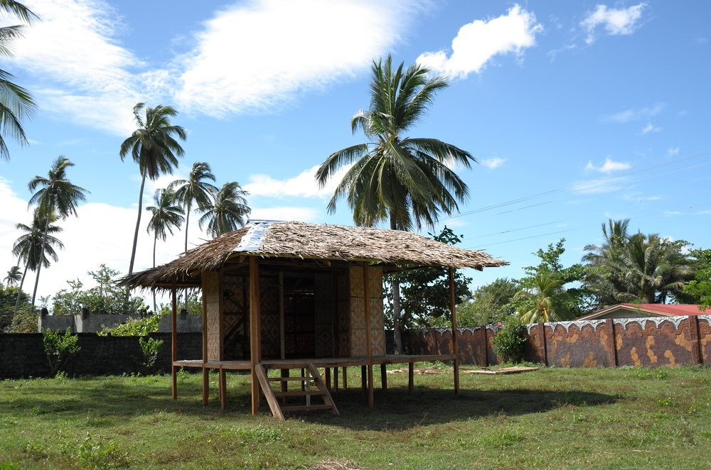 This is a full view of the hut made of wood with stilts underneath and a raised wooden platform flooring.