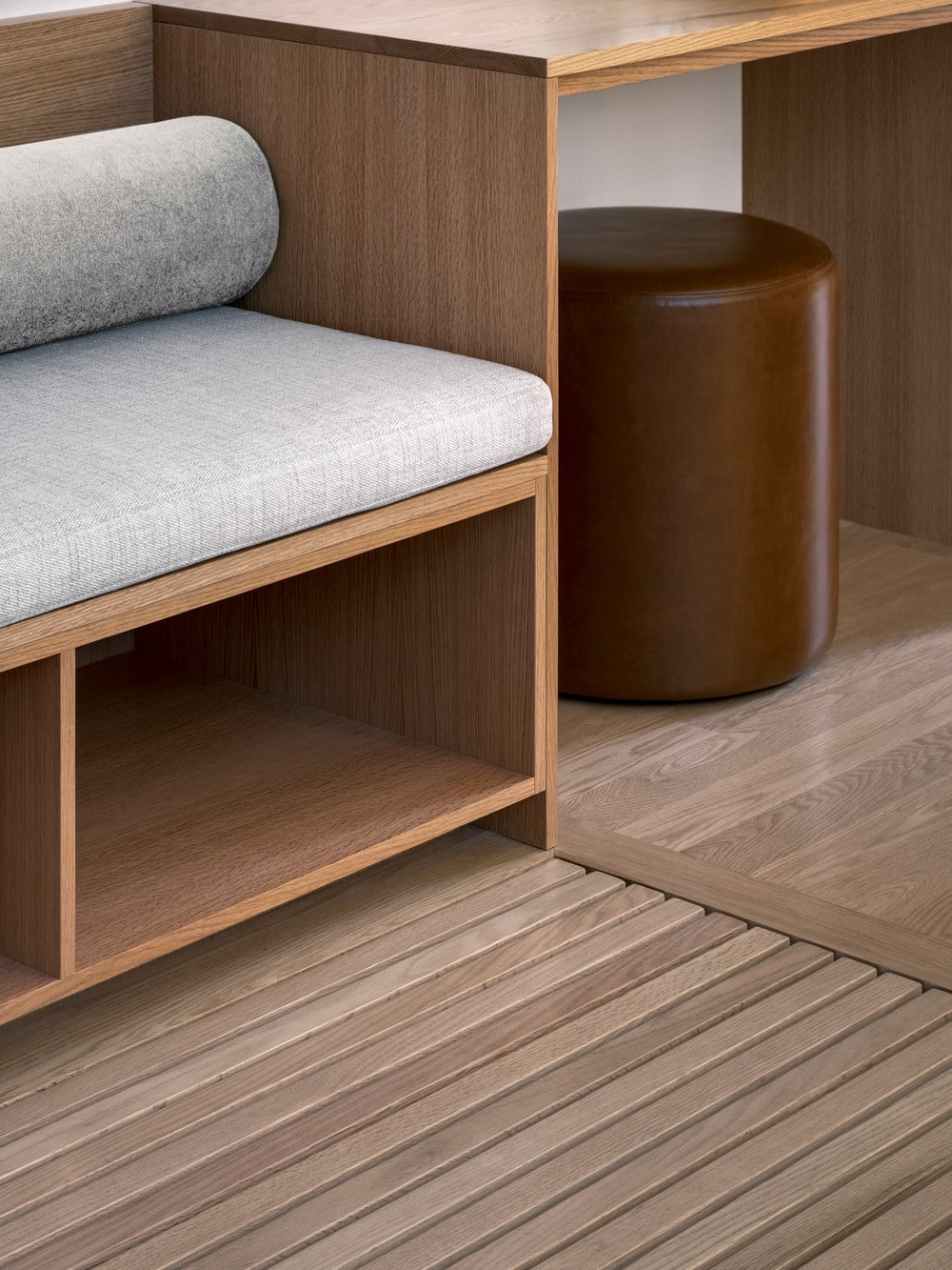 This is a close look at the built-in wooden sofa and its built-in shelving underneath for various storage.