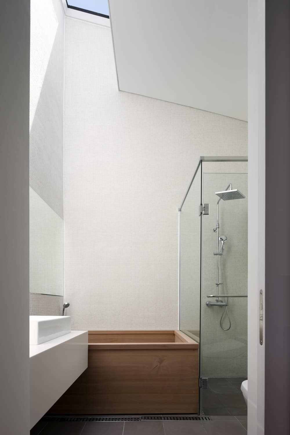 This is a close look at the primary bathroom with a tall arched ceiling, white walls, a glass-enclosed shower area and a wooden bathtub by the white sink.