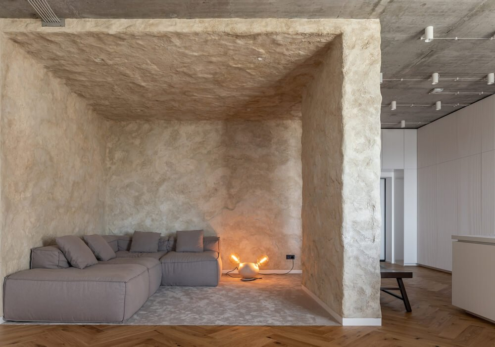 This is a full view of the minimalist living room that has textured stone walls and ceiling that makes the gray L-shaped sectional sofa stand out complemented by a modern lighting on the side.