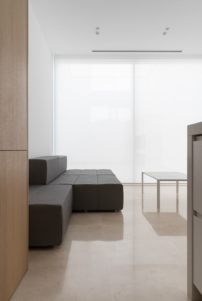 This is a close look at the living room that is dominated by the large L-shaped modern sofa that stands out against the bright walls, ceiling, floor and white coffee table.