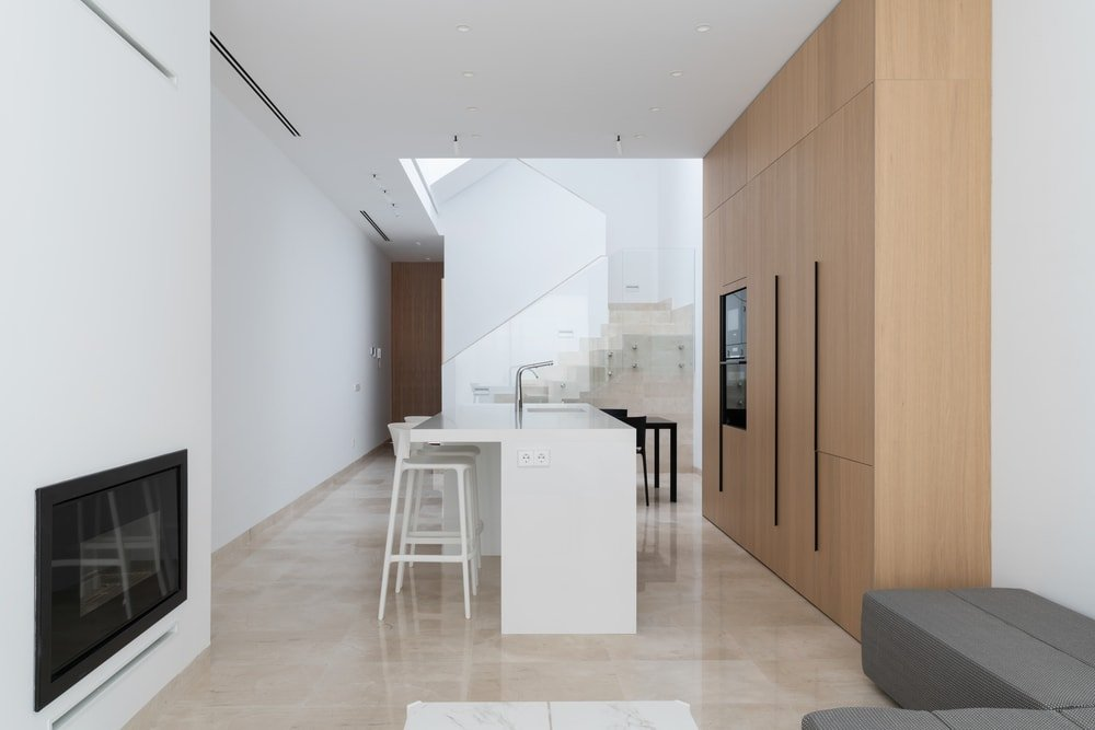 This is a look at the minimalist kitchen that has a pure white kitchen island across from the large wooden modern structure that has cabinets and embedded appliances.