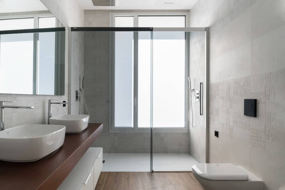 This primary bathroom has a floating two-sink vanity with a brown wooden counter that matches the floor. On the far side is the glass-enclosed shower area with a large window.