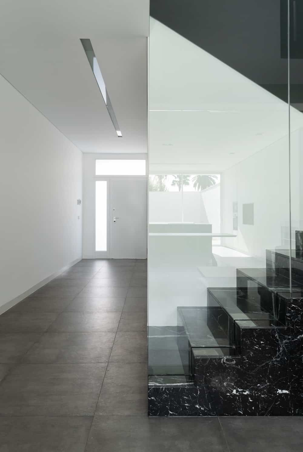 This is a simple minimalist foyer with a large white main door brightened by the side light and transom window leading to a hallway of white walls and gray flooring tiles.