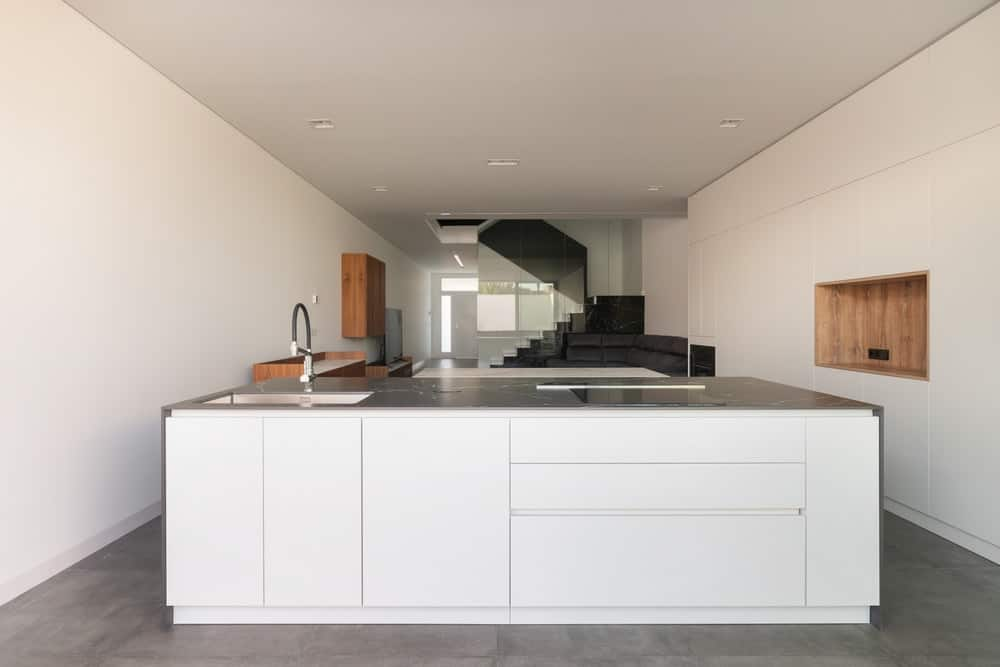 This is a close look at the minimalist kitchen that has a large white modern kitchen island that pairs well with the built-in white cabinetry lining the walls.