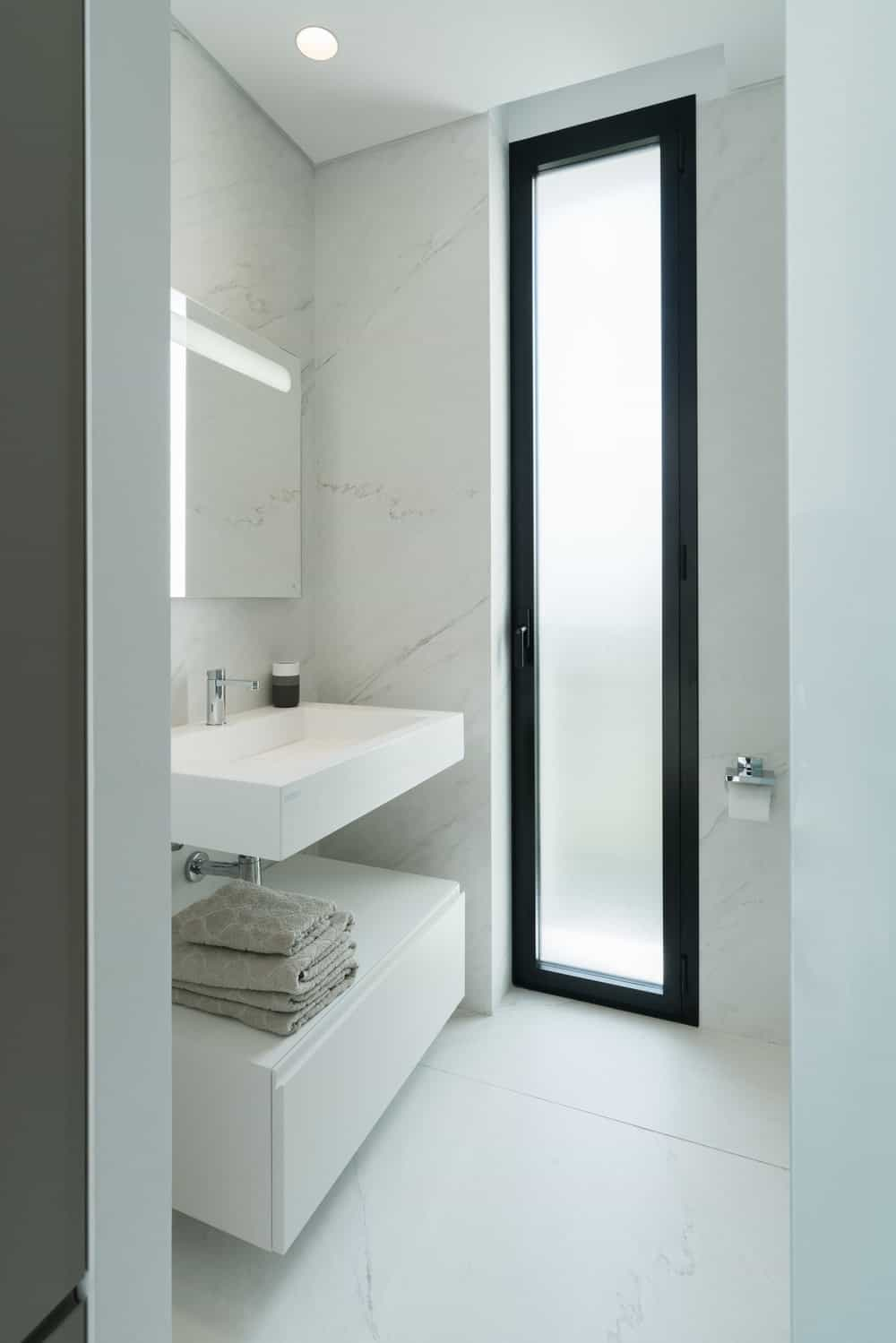 This is a simple minimalist bathroom with a pure white floating sink and vanity topped with a rimless mirror on the side of the shower area's frosted glass door.