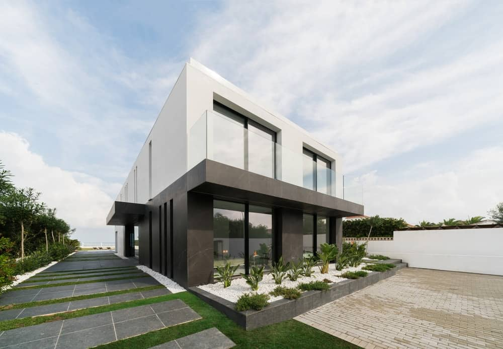 This is a look at the front of the house that has light and dark exterior walls complemented by the simple minimalist landscaping of walkways and planters with grass and shrubs.