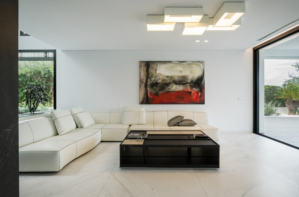 This is the bright minimalist living room that has a white L-shaped sectional sofa that matches the white walls, ceiling and floor. These are then contrasted by the wall artwork, black coffee table and the modern lighting above.