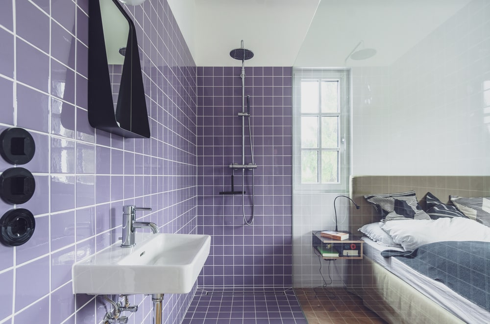 This is a close look at the bathroom with a floating sink, purple tiles and a shower area on the far side separated by glass from the bedroom.