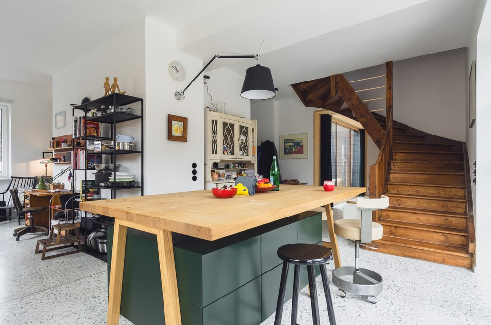 This is a close look at the rustic kitchen with a large wooden kitchen island that also serves as a breakfast bar. On the far side is the study area with a wooden desk.