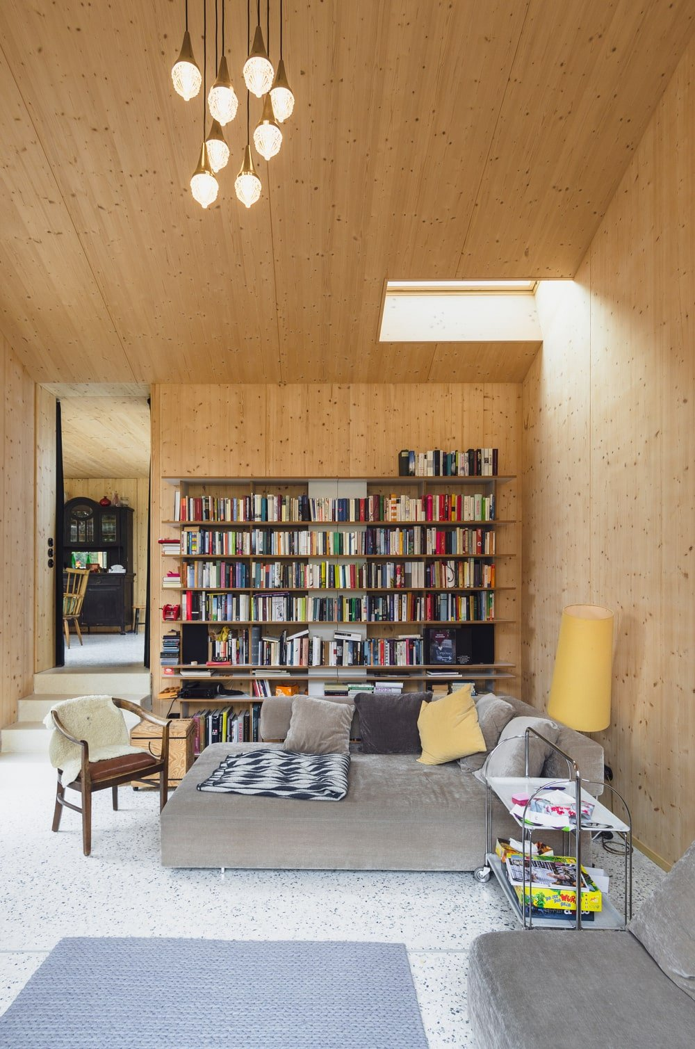 This is a close look at the living room with a gray sectional sofa, built-in bookshelves and a skylight on its tall wooden ceiling.