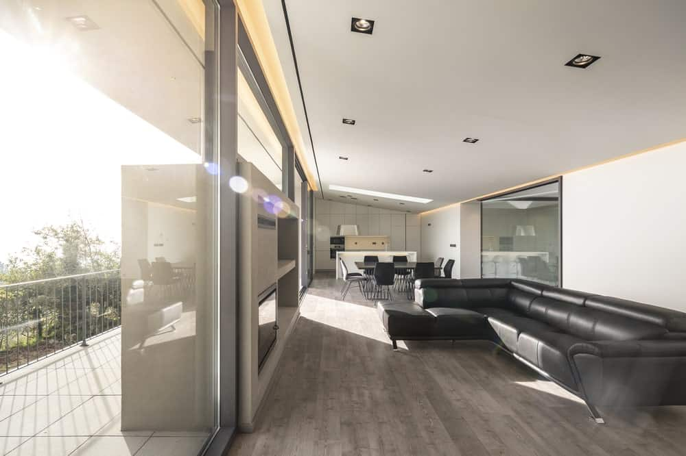 This is a close look at the living room that has a large black leather L-shaped sofa facing a large built-in concrete structure that houses the modern fireplace surrounded by glass walls.