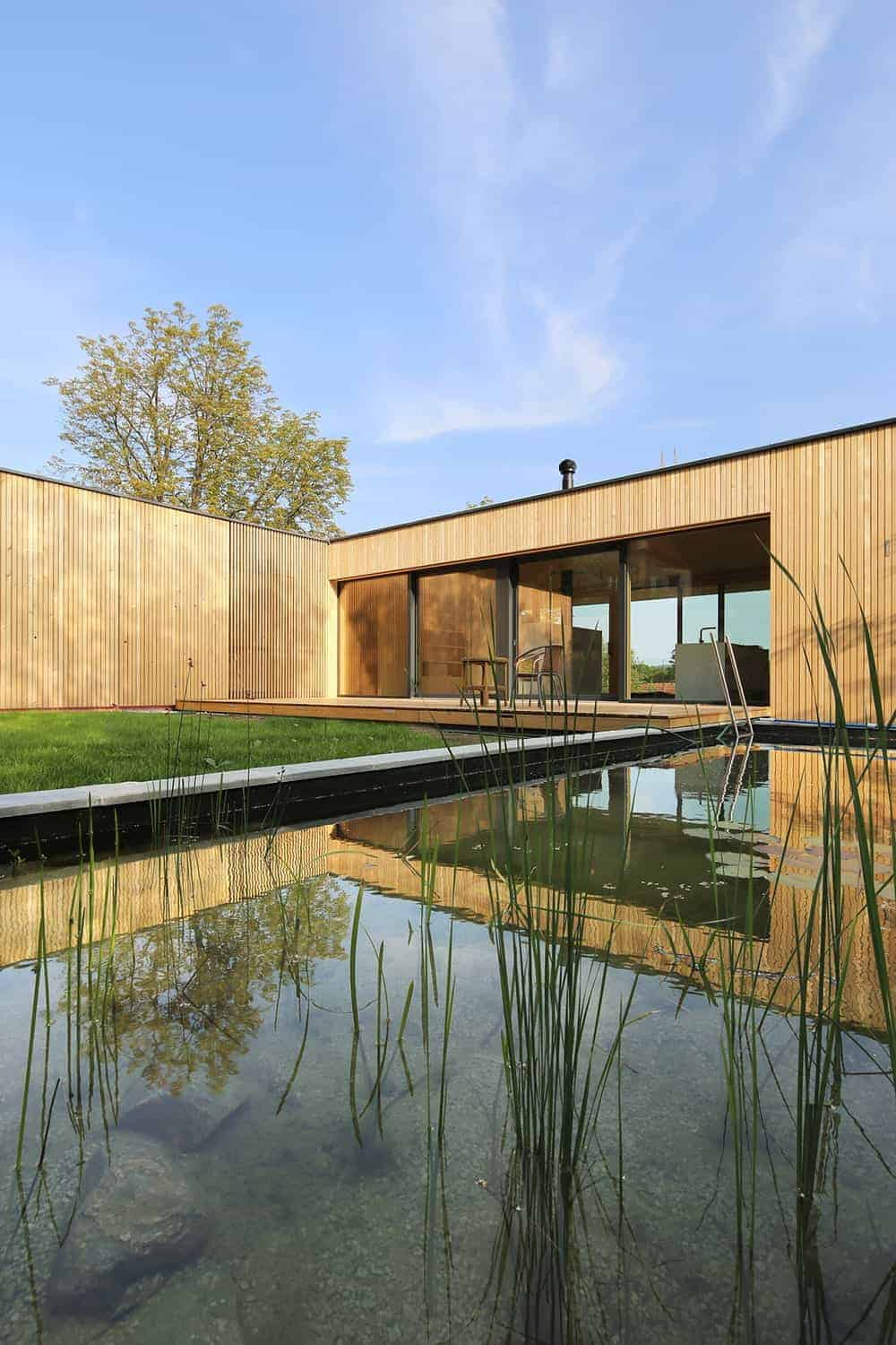 This is a minimalist landscaping that has a wooden deck patio trasitioning to a small grass lawn complemented by a small pond. These are then complemented by the wooden shiplap walls surrounding the area.
