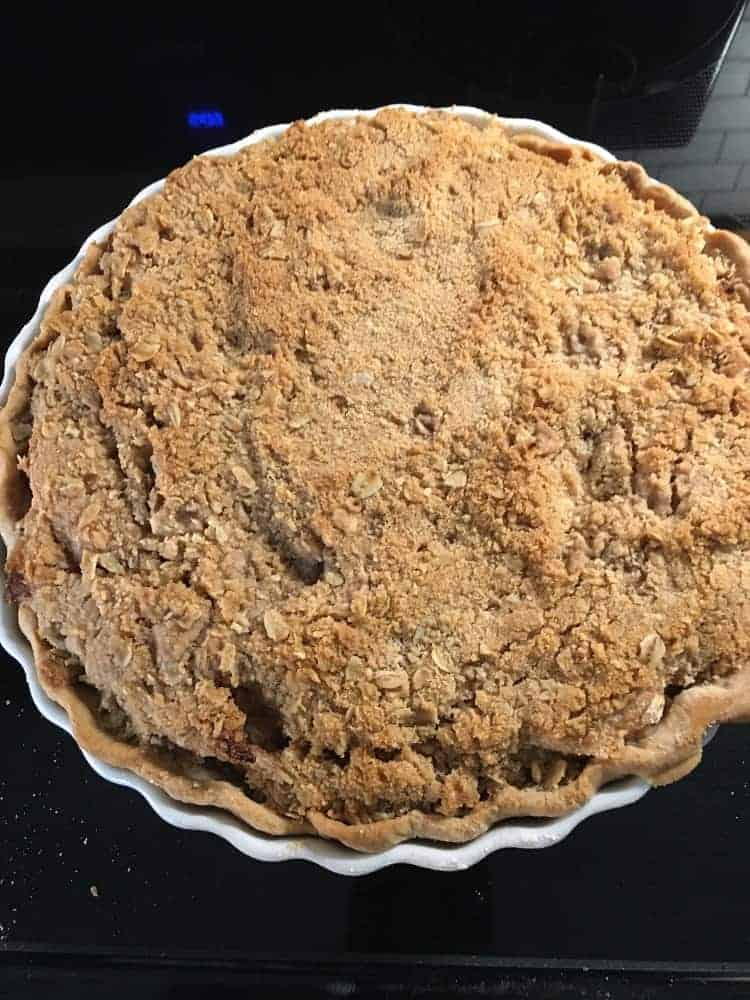 A freshly-baked batch of apple pie with crumb filling.