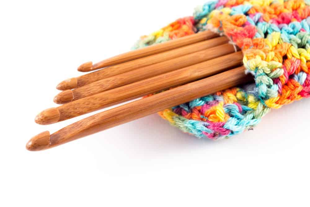 Bamboo hooks of different sizes in a small crocheted bag.