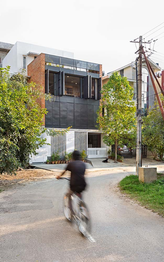 This is a street view of the house showcasing more of its black structure façade and the main entrance at the ground floor with a wide concrete driveway.