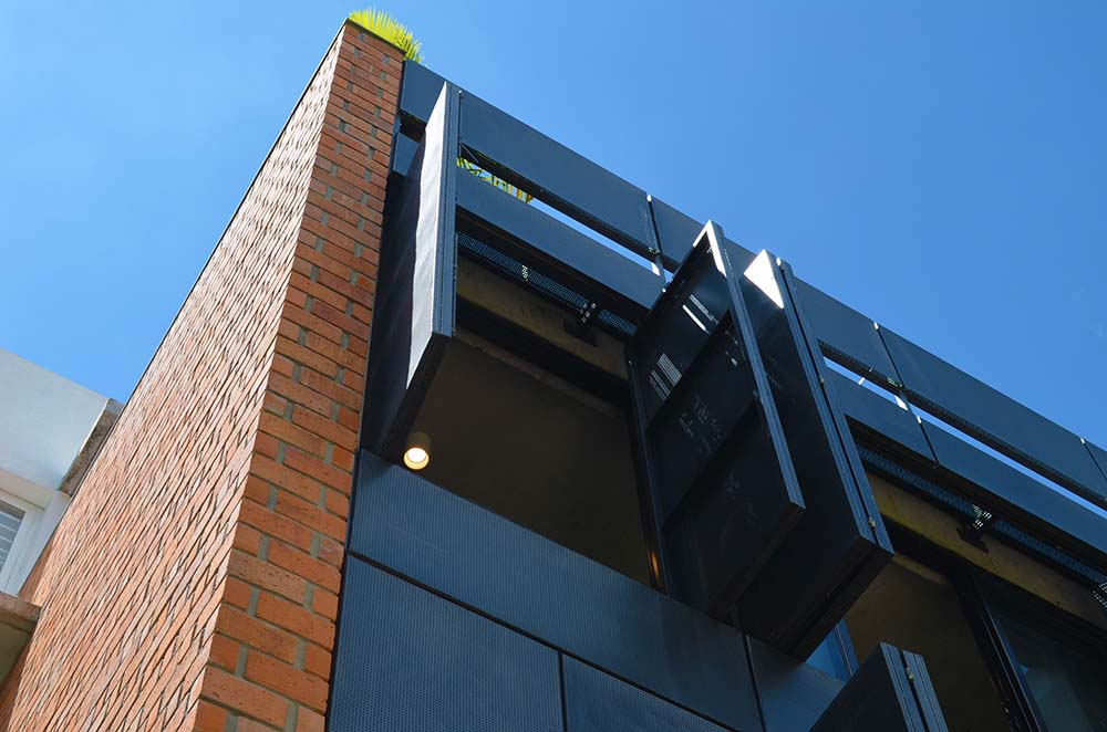 This is a closer look at the modern black window in front that contrasts the red brick wall on the side.