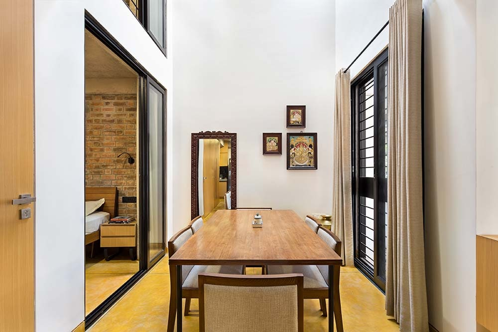 This is a close look at the dining room that has a tall ceiling, a wooden rectangular dining table and matching upholstered chairs.