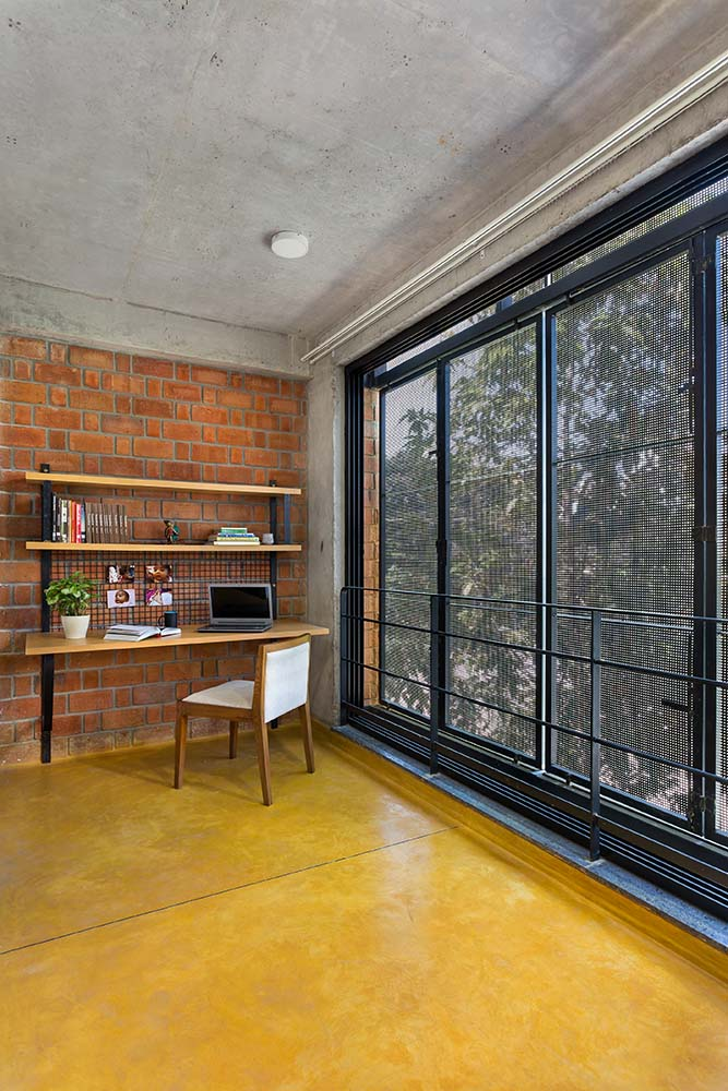 This is a close look at the study area on the far corner of the house with a built-in desk and shelf on the red brick wall by the glass windows.