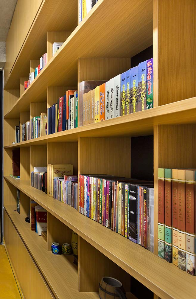 The house has a library with built-in wooden bookshelves that match the hardwood flooring.