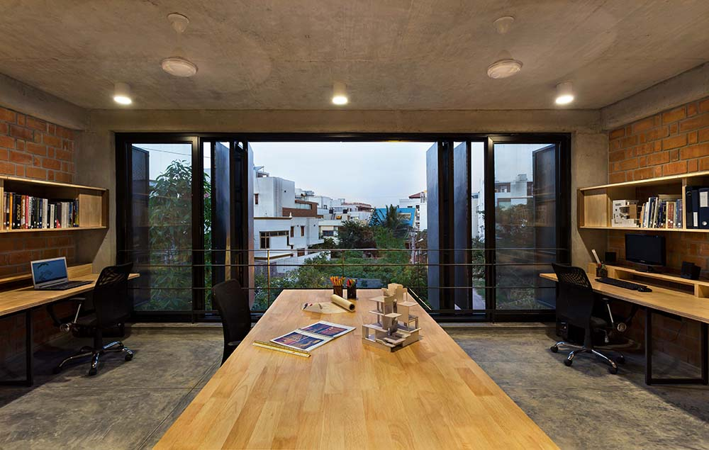 This is the home office with a couple of desks on opposite sides of the room flanking a large conference table in the middle brightened by the folding glass walls on the far side.