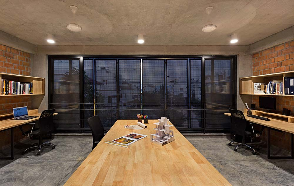 This is a look at the home office with its large conference table and desks complemented by the folding windows closed on the far side.