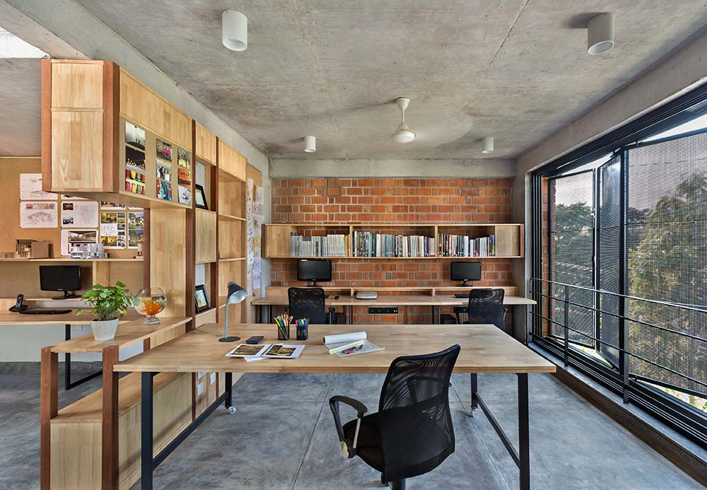 This is a closer look at the wooden conference table of the home office attached to the built-in wooden structure that has shelves and cabinets and serves as a divider.