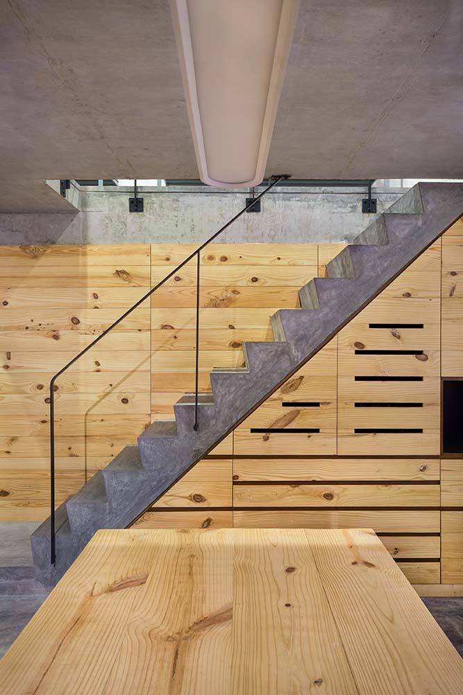This is a close look at the staircase that has wooden cabinets and drawers underneath and glass railings on its side.