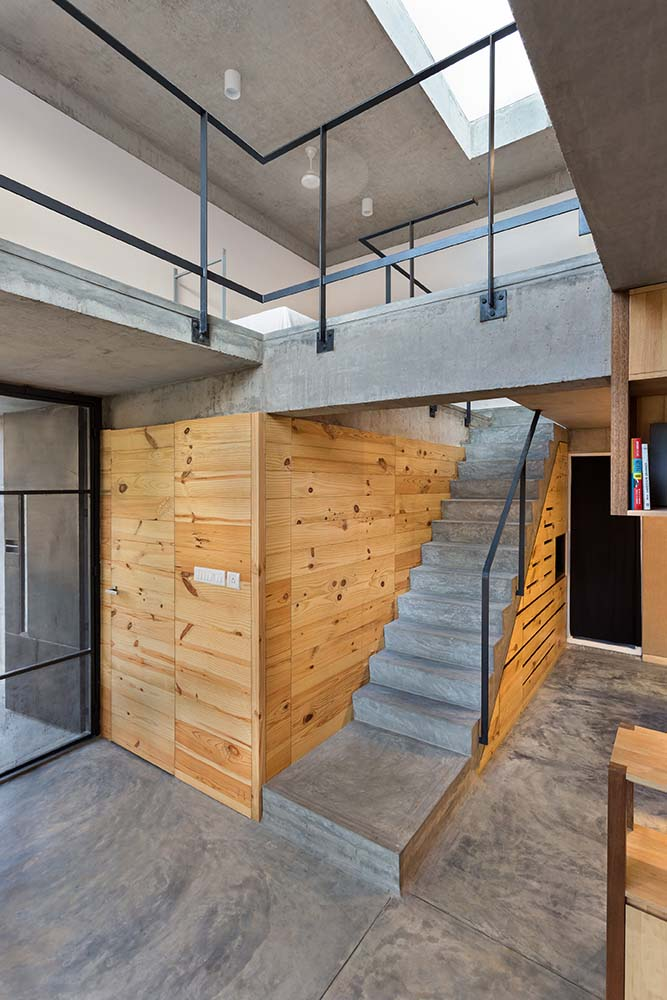 This is a close look at the staircase showcasing the wooden cabinets and drawers underneath and the indoor balconies at the upper level.