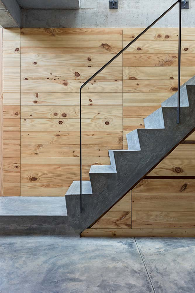 This is a close look at the modern design of the concrete steps paired iwth a wooden wall on the far side and a glass railing across from it.