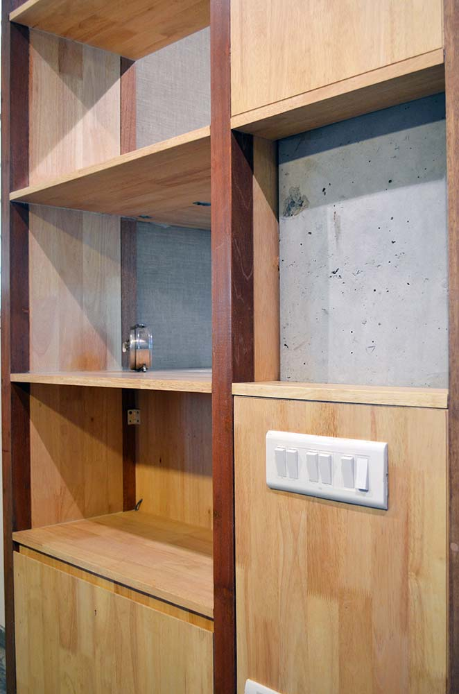 This is a close look at the built-in wooden structure on the side of the office with shelves and cabinets.