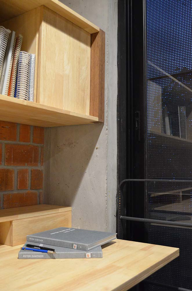 This is a closer look at the far corner desk with a built-in wooden shelf above and a red brick wall.