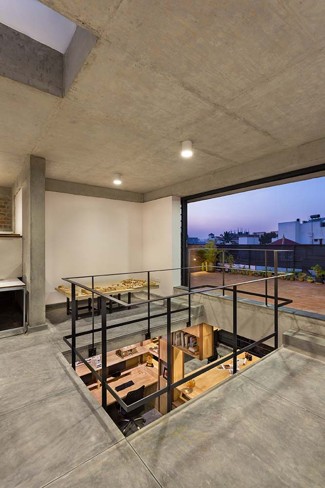 This is a close look at the indoor balcony looking over the office area and a walkway that leads to the terrace balcony.
