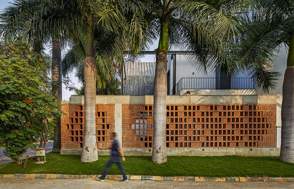 This is a close look at the side of the house with consistent red brick slatted panels on the ground floor adorned by the landscaping of tall tropical trees.