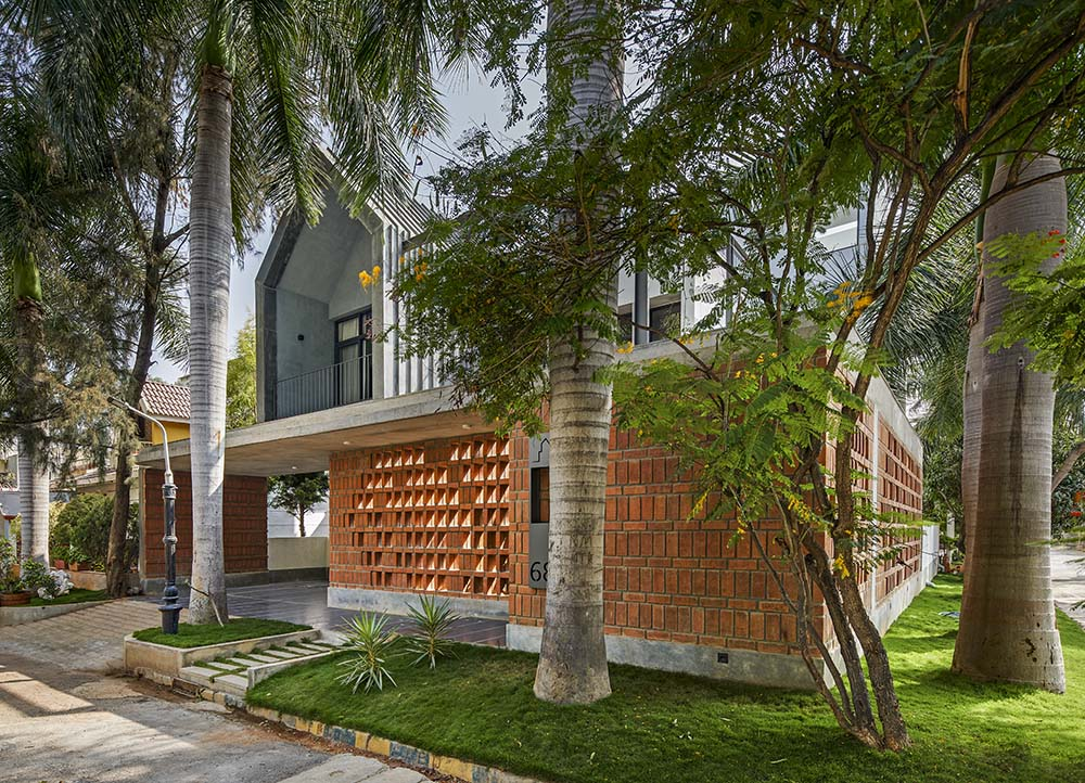 This is another look at the front of the house showcasing more of the landscaping of tall tropical trees and well-manicured grass that complement the red brick panels.