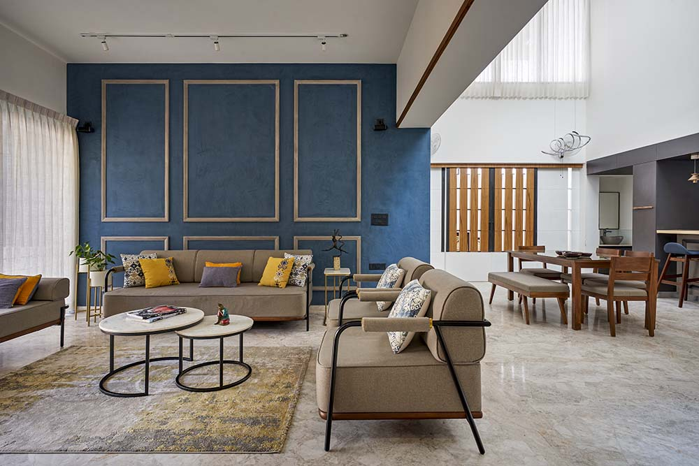 This is a close look at the living room that has beige sofas, white multi-tiered coffee tables and a blue wall on the far side.