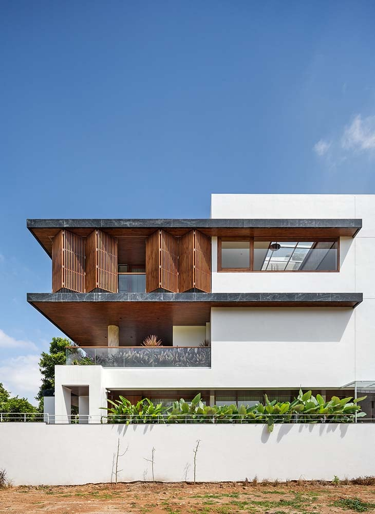 This is a close look at the house exterior that showcases the semi-open slat wood panels of the upper floor.