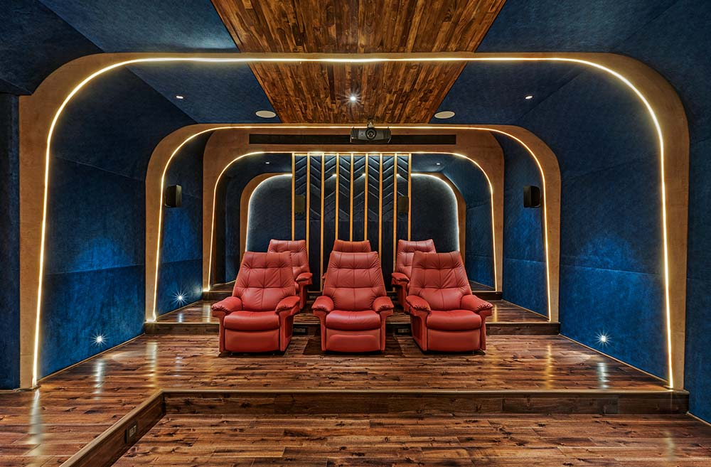 This is the home theater with red leather armchairs that stand out against the surrounding blue green walls and ceiling that has golden accents.