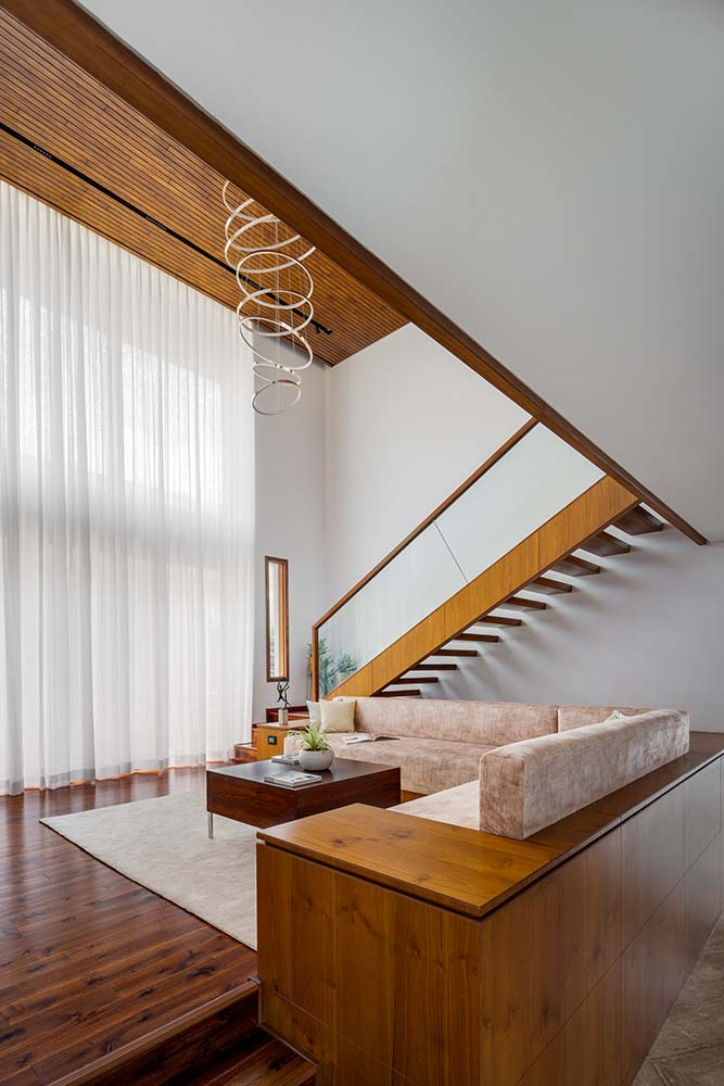 The living room is placed just on the side of the staircase with a large L-shaped sofa.