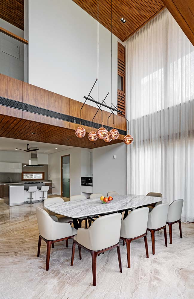 This is a close look at the dining area with a large white dining table surrounded by cushioned chairs and topped iwth a decorative chandelier.