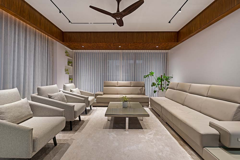 This is a sitting room with large gray sofas and gray armchairs surrounding a large gray coffee table topped iwth a ceiling fan.