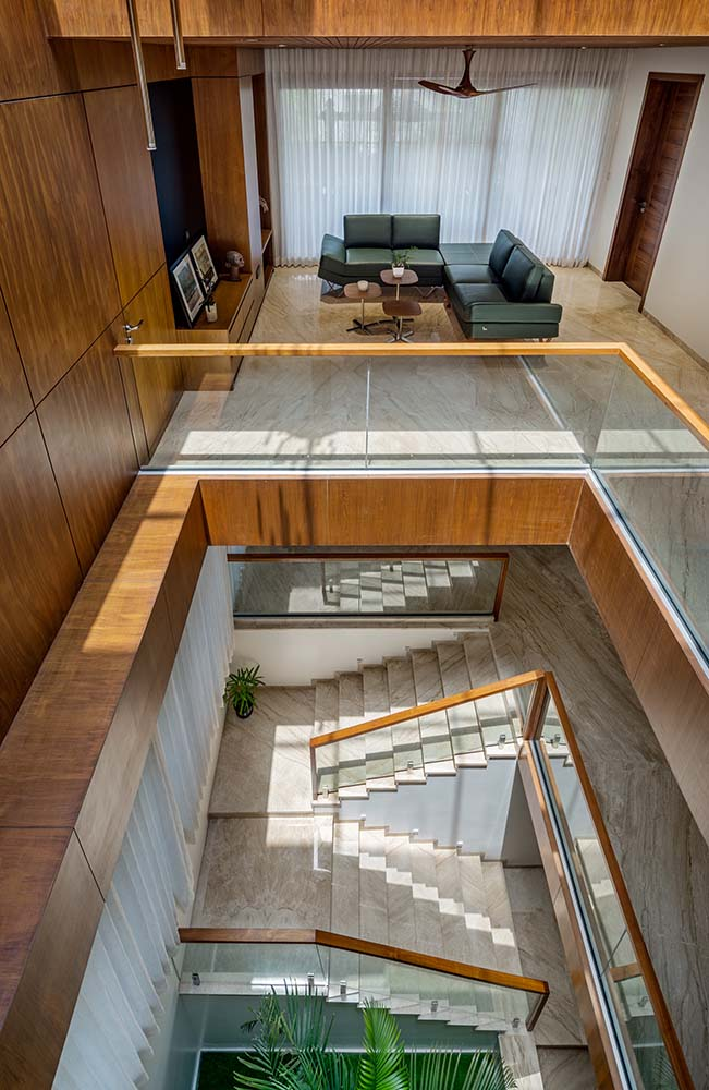 This is a close look at the indoor balcony that has glass railings on the side and has a view of the lower level.