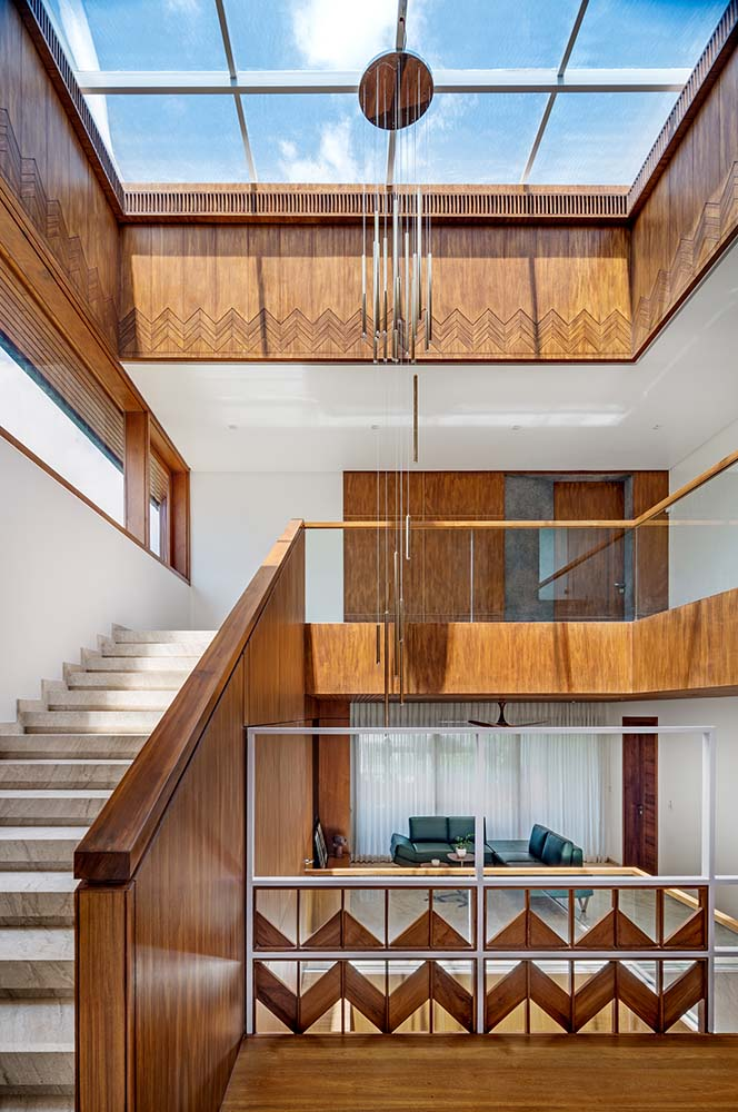 This is a look at the top floor landing with a large skylight in the middle of the staircase atrium that hangs a decorative lkighting in the middle.